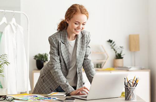 happy fashion designer working on laptop replying H3X679A