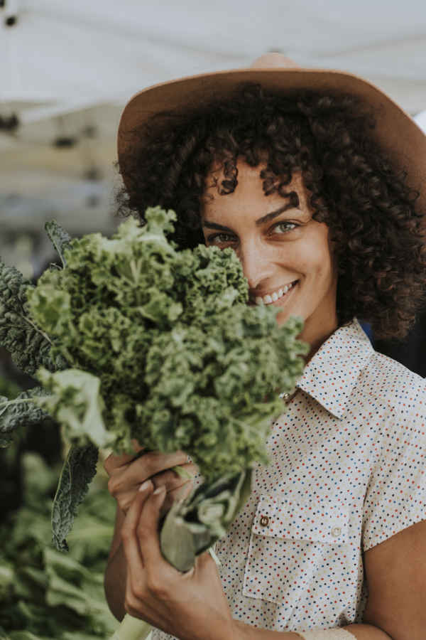 beautiful woman buying kale at a farmers market WD9M6G8 1