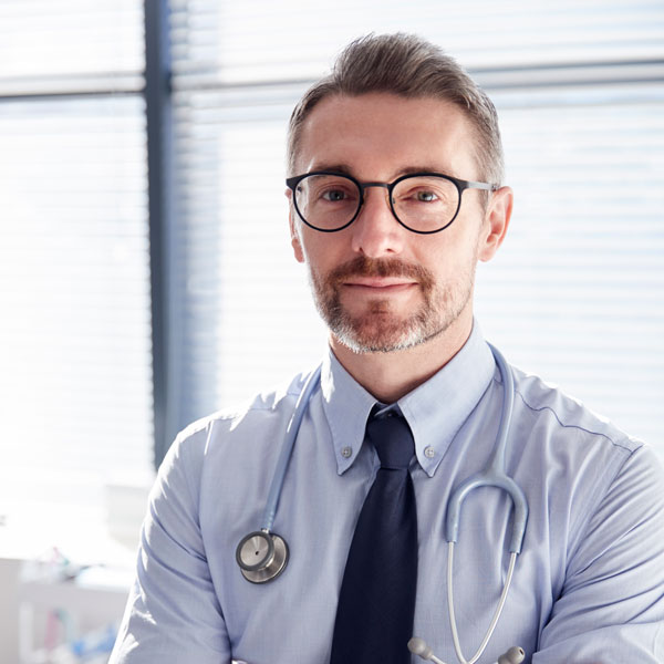 portrait of smiling mature male doctor with stetho J2MWQDT