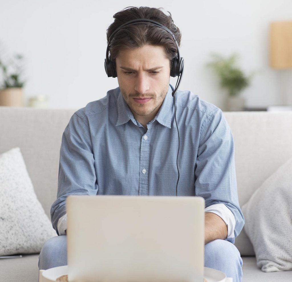 serious student in headphones studying at laptop a Z8PFWB5