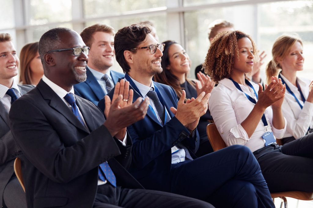 smiling audience applauding at a business seminar PLQAUXK