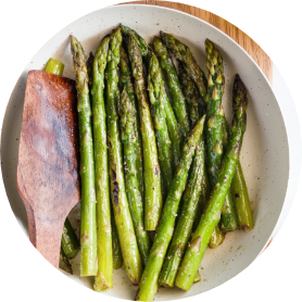 Top view on roasted asparagus in a white pan on a kitchen table. Modern style vegetarian food.