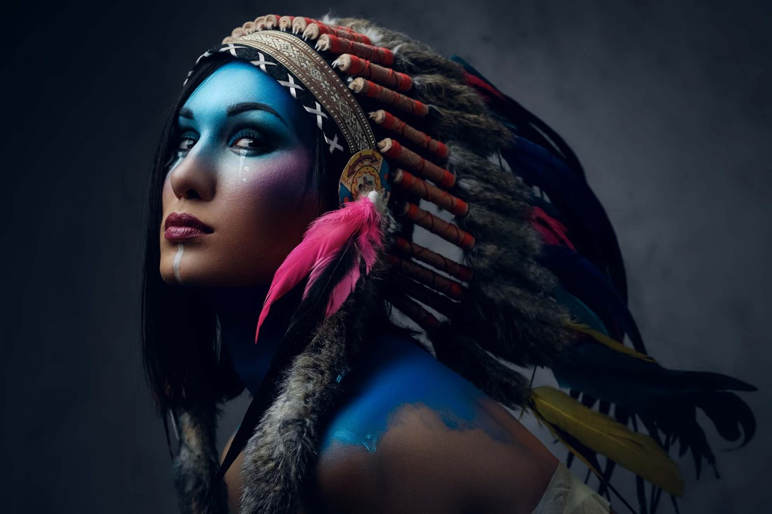 female with indian feather hat and colorful makeup UK47EWD